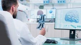 Badacz w medycyny śródpolny pisać na maszynie w komputerowej klawiaturze, patrzeje promienia obraz cyfrowego X zbiory wideo