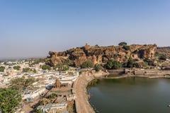 Badami - sikt av staden - bak ett enormt vaggar på kulletemplet arkivfoto