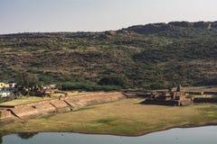 Badami tempel med den delvis torkade övre sjön - bergbakgrund fotografering för bildbyråer