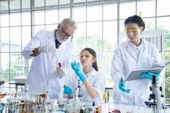 Badania Medyczne i naukowowie pracujemy z mikroskopem, tubki, mikropipeta i analiza rezultaty w a pastylki i Próbnych, obraz royalty free