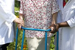 Badante che aiutano un paziente senior con il suo camminatore all'aperto Fotografia Stock Libera da Diritti