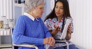 Badante messicano che parla con la compressa con il paziente senior fotografie stock