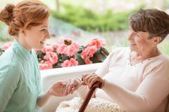 Badante sorridente che sostiene donna senior felice con lo sti di camminata immagini stock