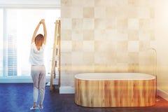 Badar det vita lyxiga badrummet för vinden som är trä, kvinnan Arkivfoto