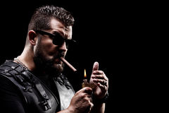 Badass biker lighting up a cigarette. On black background stock image