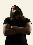 A badass is looking at you challenging you!. Muscular man looking like a rock star with a black t-shirt with long, beautiful, luscious hair looking forward. Low Royalty Free Stock Images
