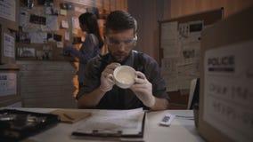 Badawczy specjalista bierze odciski palca od białej filiżanki na stole zbiory