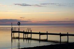 Badbrücke mit lifebouy im Sonnenuntergang und im ruhigen Wasser Stockfotografie