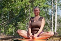 Baddha Konasana. The woman trains yoga in wood. A pose Baddha Konasana Royalty Free Stock Photos