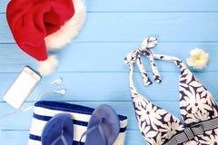 Baddräkt för kvinna` s och strandtillbehör med den bästa sikten för Santa Claus hatt, lekmanna- lägenhet, kopieringsutrymme Julse royaltyfri bild