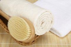Badebürste und gerolltes Tuch in einem Korb Stockbild