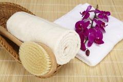 Badebürste und gerolltes Tuch in einem Korb Stockfoto