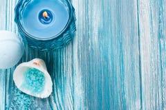 Badebombenahaufnahme mit blauer brennender Kerze stockbilder