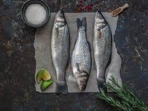 Badejo de três peixes crus e outros ingredientes no fundo escuro do vintage Imagens de Stock