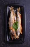 Badejo fritado dos peixes em uma placa preta Imagens de Stock