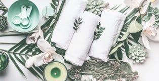 Badekureinstellung mit Tüchern, grüne Kerze, tropische Blätter, weiße Orchidee blüht, Draufsicht stockfoto