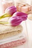 Badekurort eingestellt: Blumenstrauß von Tulpen auf einem Tuch, Seesalzen und Stück Seife Stockfoto