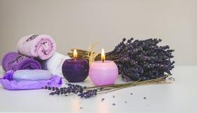 BADEKURORT eingestellt mit Lavendelseife, der exfoliating Massage, die Handschuh abziehen, rosa Tuch und Kerzen lizenzfreies stockfoto