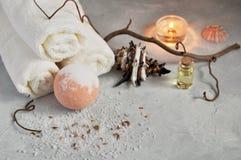 Badekurort entspannen sich Konzept Weiße Frotteestoffe, Steine, eine Kerze und eine Bombe für ein Bad des Seesalzes auf einem gra stockbild