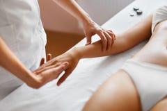 Badekurort - 7 Frauenfuß im Wasser Massage der menschlichen Hand im Badekurortsalon Stockfotografie