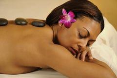 Badekurort-heiße Mineralsteinmassage mit Blume im Haar Lizenzfreie Stockfotos