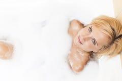 Badekurort-Konzept und Ideen Junges kaukasisches blondes weibliches, Entspannungs-Badewanne mit Schaum habend Lizenzfreie Stockfotos