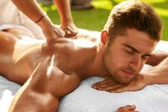 Badekurort-Körper-Massage Mann, der draußen entspannende Rückenmassage genießt Stockbilder