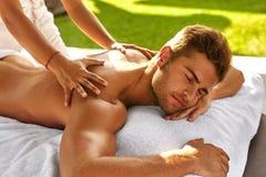 Badekurort-Massage für Mann Mann, der die entspannende Rückenmassage im Freien genießt Stockbild