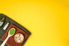 Badekurort oder Wellnesseinstellung in den grünen Farben Flaschen mit wesentlichem Aroma ölen, Tücher, Seesalz auf gelbem Hinterg Lizenzfreies Stockbild