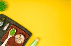 Badekurort oder Wellnesseinstellung in den grünen Farben Flaschen mit wesentlichem Aroma ölen, Tücher, Seesalz auf gelbem Hinterg Stockbilder