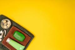 Badekurort oder Wellnesseinstellung in den grünen Farben Flaschen mit wesentlichem Aroma ölen, Tücher, Seife auf gelbem Hintergru Stockfoto