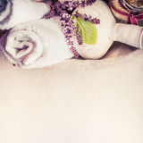 Badekurort oder Wellnesshintergrund mit Kräutermassagekompressenbällen, Tuch und frischen Kräutern stockfoto