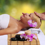 Badekurort. Schöne Blondine, die Gesichtsmassage erhalten. Im Freien lizenzfreies stockbild