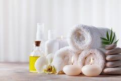 Badekurort, Schönheitsbehandlung und Wellnesshintergrund mit Massagekieseln, Orchideenblumen, Tücher, kosmetische Produkte und br lizenzfreies stockfoto