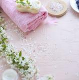 Badekurort Tuch, Seesalz und Seife Rosa Hintergrund und Blumen Platz für Text Lizenzfreie Stockfotos