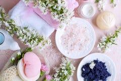 Badekurort Verschiedene Kosmetik für Sorgfalt und Schönheit Rosa Hintergrund und Blumen Platz für Text Der geschlossene Aufbau Stockbild