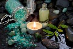 Badekurortanordnung - natürliches Massageöl mit einer brennenden Kerze Stockfoto