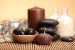 Badekurortbehandlung - schwarze Steine und Kerzen Lizenzfreies Stockfoto