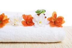 Badekurortdetail. Tuch und Blumen mit Steinen Stockfotografie