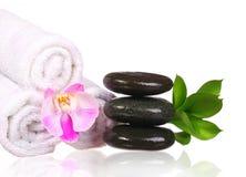 Badekurorteinstellung. Badekurort-Steine und rosa Orchideen-Blume mit grünen Blättern Stockfotografie