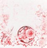 Badekurorteinstellung mit Rosen, ätherischem Öl und den sich hin- und herbewegenden Blumenblättern auf hellem Pastellhintergrund, Stockfotos