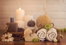 Badekurorteinstellung mit Tüchern, Öl und hölzernem Herzen auf weißem Ziegelsteinhintergrund Stockfoto