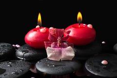 Badekurorteinstellung von roten Kerzen auf Zensteinen mit Tropfen, Orchidee Stockfotos