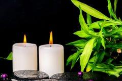Badekurorteinstellung von Zenbasaltsteinen mit Tropfen, weiße Kerzen, Perle Stockbild