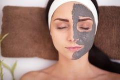 Badekurortfrau, die Gesichtsreinigungsmaske anwendet Schönheits-Behandlungen Lizenzfreies Stockfoto