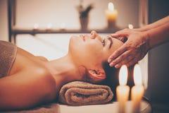 Badekurortgesichtsbehandlung Massage Brunettefrau, die entspannende Gesichtsmassage genießt stockfotografie