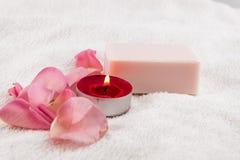 Badekurortkonzept mit rosafarbener Seife auf dem weißen Tuch verziert durch Schneiderflorida Stockfoto