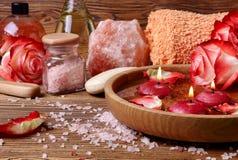 Badekurortkonzept mit Rosen, rosa Salz und Kerzen, die in wate schwimmen Stockbilder