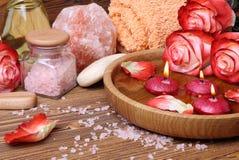 Badekurortkonzept mit Rosen, rosa Salz und Kerzen, die in wate schwimmen stockbild