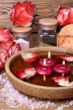 Badekurortkonzept mit Rosen, rosa Salz und Kerzen, die in wate schwimmen Stockfoto